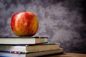 Die 10 beliebtesten Studiengänge in Deutschland - Ein roter Apfel sitzt auf einem Holztisch - Cochrane & Porter Versicherungsagentur